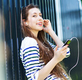 Young woman listening to music with smartphone Stock Photos
