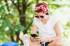 Young woman listening to the music on the smartphone. In the park Stock Images