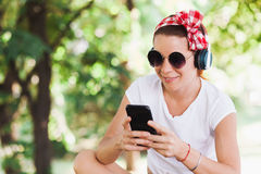 Young woman listening to the music on the smartphone. In the park Royalty Free Stock Photo