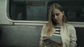 Young woman listening to music on train using tablet computer, student girl after lessons in subway wagon with laptop pc. Young woman listening to music on train stock footage