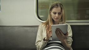 Young woman listening to music on train using tablet computer, student girl after lessons in subway wagon with laptop pc. Young woman listening to music on train stock video footage
