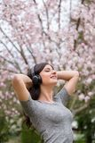 Young woman listening to music on wireless headphones in a park with cherry blossom trees. stock photography