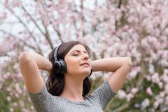 Young woman listening to music on wireless headphones in a park with cherry blossom trees. royalty free stock photo