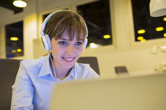 A young woman listening to music at work Stock Photo