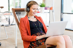 Young woman listening to the music while working on a computer Stock Photos