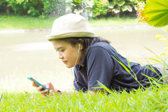 Young woman listening to music from your smart phone on the gras Stock Photo