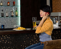 Young woman listening to a phone call. Young woman sitting at a bar counter in a nightclub listening to a phone call on her mobile phone looking at the camera stock photos