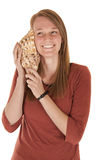 Young woman listening to a seashell smiling Royalty Free Stock Image