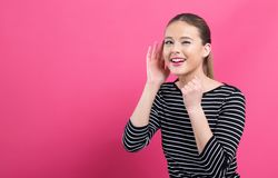 Young woman listening. On a pink background royalty free stock photography