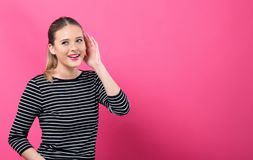 Young woman listening. On a pink background stock photography