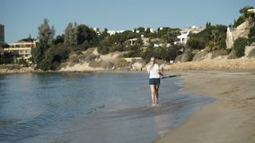 Young woman listens music and runs along the beach near the ocean stock video