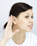 The young woman listens Stock Photography