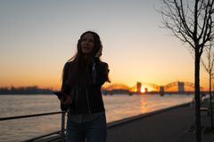 Young woman listens to music in closed headphones through her phone wearing a leather jacket and jeans at a sunset near stock photography