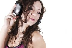 The young woman listens to music in ear-phones Stock Image