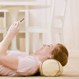 Young woman listens to music on mp3 player Royalty Free Stock Photography