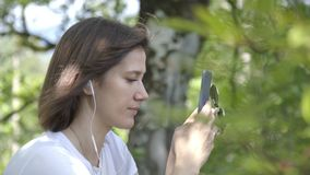 Portrait of Young woman listens to music with phone and headphones enjoying sound park forest background. Young woman stock footage