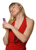 The young woman listens to music from a player Royalty Free Stock Photography