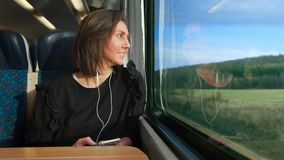 Woman listens to a player and goes on a train in Europe