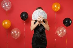 Young woman in little black dress hiding, covering face with bundle lots of dollars, cash money in hands on bright red. Background air balloons. Happy New Year royalty free stock images