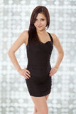 Young woman in a little black dress smiles with confidence. Stock Photography