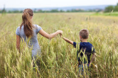 Young woman and little boy her son  standing in wheat field. Uni Stock Photography