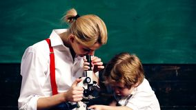 Young woman with a little boy looking at a wheat stem in a microscope on a green board background. Teacher and student