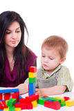 Young woman and little boy playing wooden cubes Stock Photo
