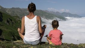 Young woman with little cute daughter meditating on top of the mountain. stock video footage