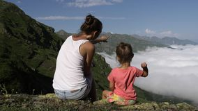Young woman with little cute daughter sitting on top of the mountain. stock video footage