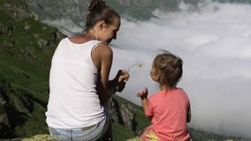 Young woman with little cute daughter sitting on top of the mountain. stock footage