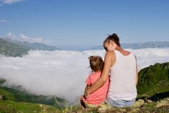 Young woman with little cute daughter sitting on top of the mountain. Young women with little cute daughter sitting on top of the mountain. Family higher than Stock Images