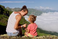 Young woman with little cute daughter sitting on top of the mountain. Young women with little cute daughter sitting on top of the mountain. Family higher than Stock Photos