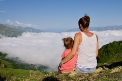 Young woman with little cute daughter sitting on top of the mountain. Young women with little cute daughter sitting on top of the mountain. Family higher than Stock Photography