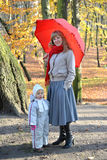 The young woman with the little daughter stand under a red umbrella in the autumn park Royalty Free Stock Image