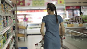 Young woman with little daughter in trolley walking at the supermarket. Back view of young woman with little daughter in trolley walking at the supermarket stock video