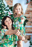 A young woman and a little girl in bright dresses show a thumbs-up. Mom and daughter royalty free stock photos