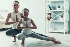 Young Woman and Little Girl doing Yoga Pose royalty free stock photos