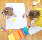 Young woman and little girl drawing Royalty Free Stock Images