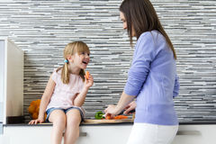 Young woman and little girl eating carrots in the kitchen. Portrait of  young women and little girl eating carrots in the kitchen Royalty Free Stock Images
