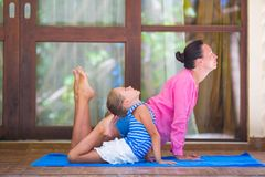 Young woman and little girl engaged in fitness stock photos