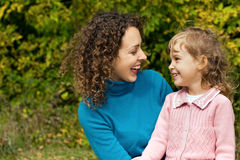 Young woman and little girl laugh in garden Stock Photo