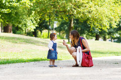 Young woman and little girl of one year walking through summer p Stock Photo