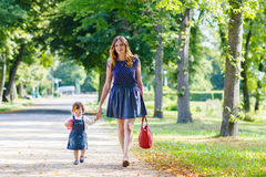 Young woman and little girl of one year walking through summer p Stock Photos