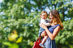 Young woman and little girl of one year walking through summer p Royalty Free Stock Images