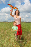 Young woman and little girl plays kite on meadow Royalty Free Stock Photos