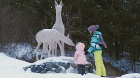 Young woman with daughter stay near statue of a deer. Young woman with little girl wearing winter clothes stay near statue of deer. Snowfall landscape stock footage