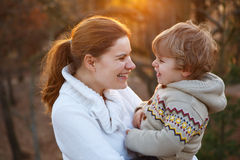 Young woman and little son hugging in evening light Stock Photos