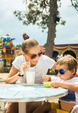 Young woman little son at the table in cafe in amusement park Stock Photos