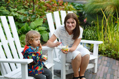 Young woman and little toddler boy eating ice cream outdoors Royalty Free Stock Images