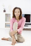 Young woman on living room floor Royalty Free Stock Image